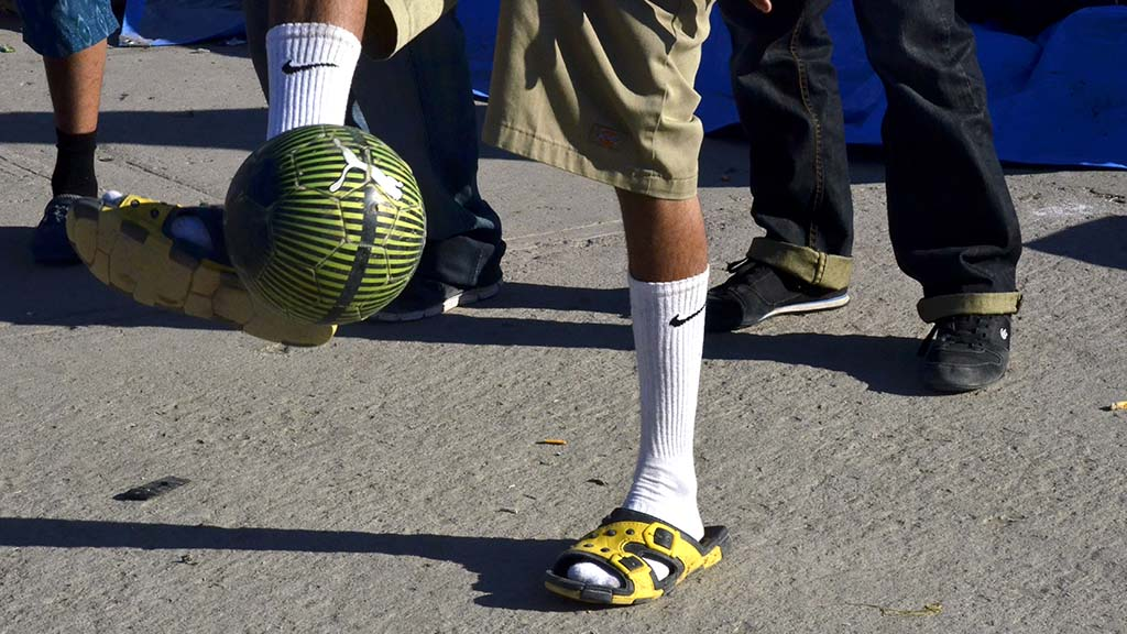 A man plays soccer in sandals. New shoes is one of the most requested item at the shelter.