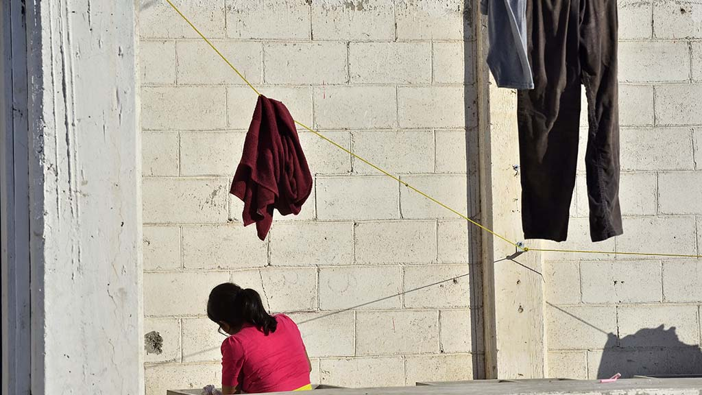 A migrant living at El Barretal shelter washes her clothes in the courtyard area.