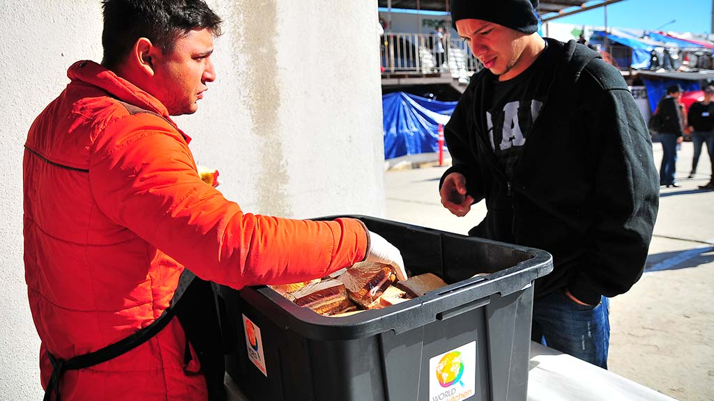A World Central Kitchen worker hands out a sandwich to a migrant shelter resident in the afternoon.
