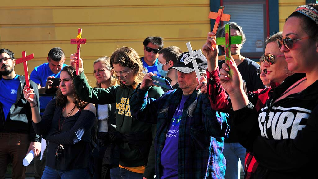 Volunteers hold crosses as they have a moment of silence for migrants who died recently.