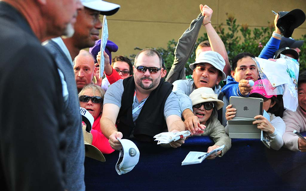 Tiger Woods passes beseeching autograph seekers at Farmers Insurance Open.
