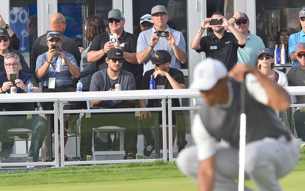 Beer-drinking fans watch Tiger Woods line up putt on Day 1 of Farmers Insurance Open.