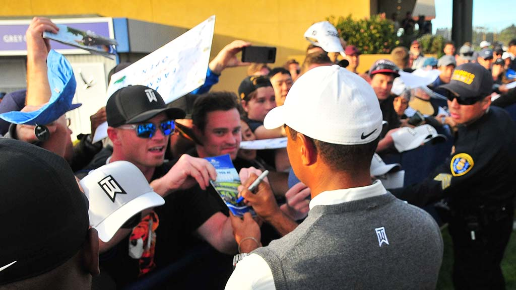 Tiger Woods signs all manner of materials at Farmers Insurance Open.