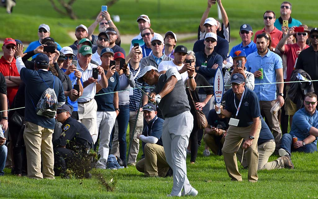 Tiger Woods sprays fairway grass on Day 1 of Farmers Insurance Open.