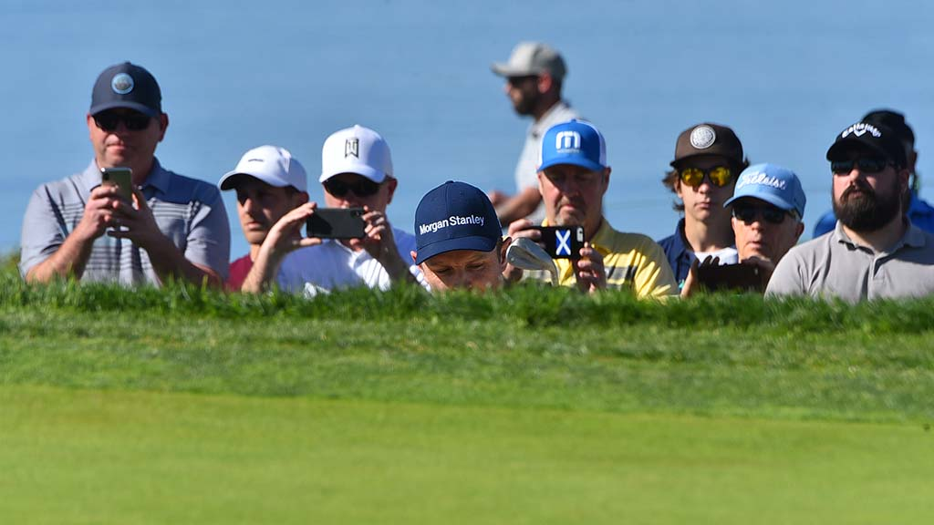 Justin Rose (center) is almost a part of the crowd as he chips onto the green of the 5th hole in the Farmers Insurance Open.