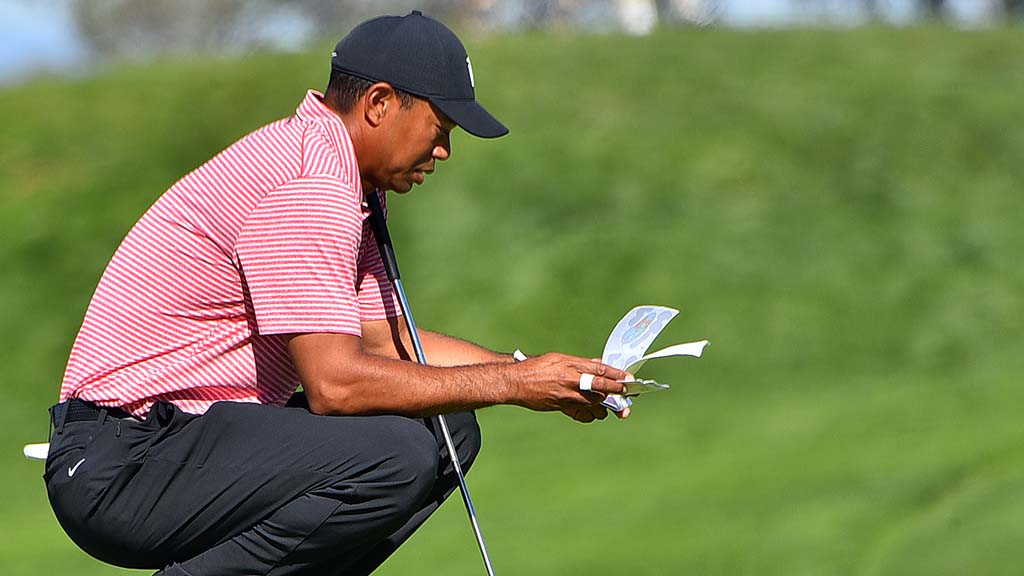 Tiger Woods looks over his tournament booklet while waiting on the 2nd hole at the Farmers Insurance Open.