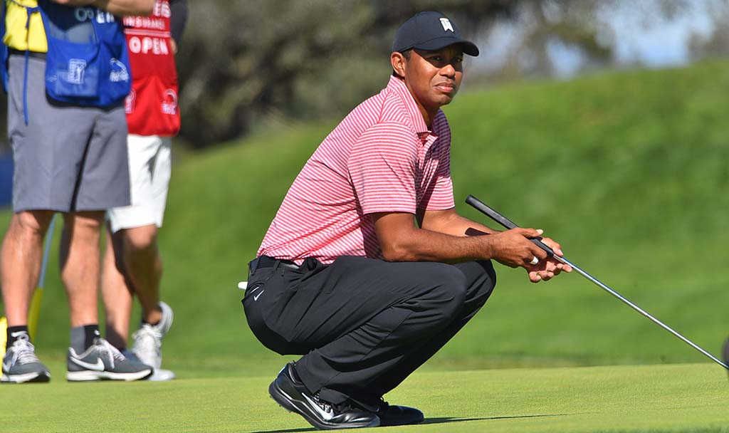 While waiting on the 2nd hole, Tiger Woods watches the play of the leaders on the nearby 6th hole on the south course.