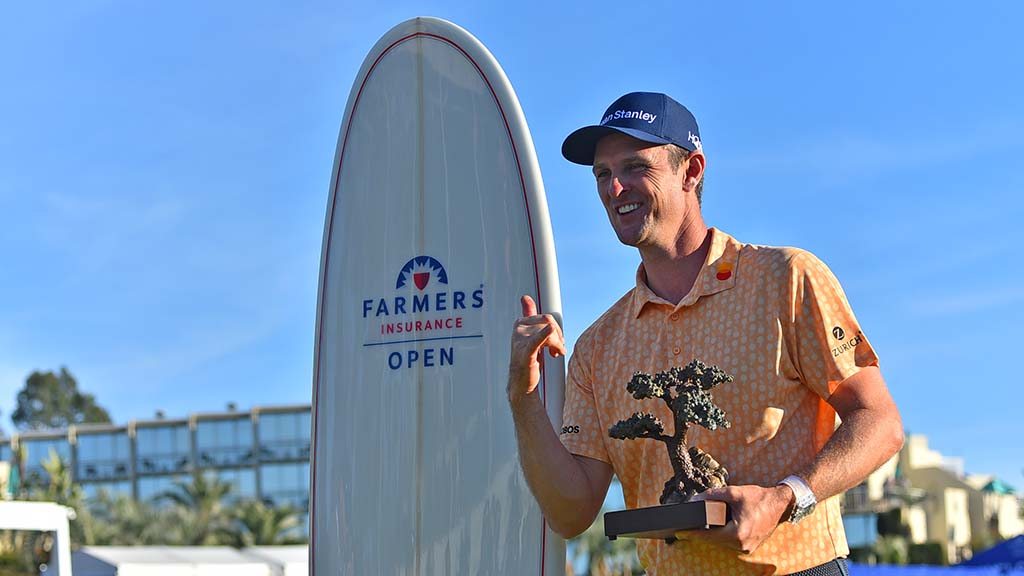Justin Rose poses with his trophy and surfboard after winning the Farmers Insurance Open, shooting 21 under par.
