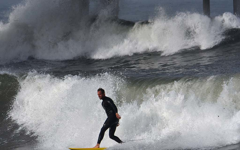 A surfer enjoys the king tides at high tide at Ocean Beach Pier.