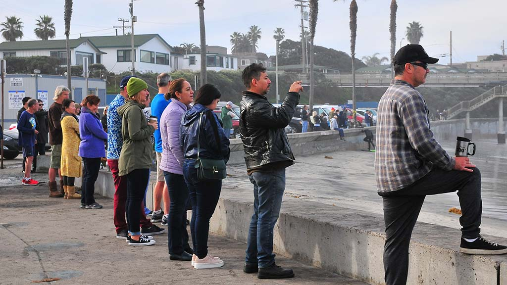 People line up along the Ocean Beach sea wall to watch the king tides slam into the pier early at high tide.