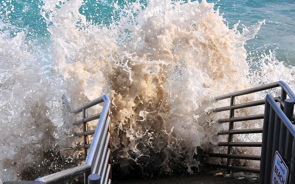 Waves from the king tide slam into the staircase at La Jolla Cove.