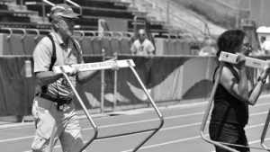 USATF national masters chairman Rex Harvey helps Marilyn Mitchell remove hurdles at 2018 national championships.