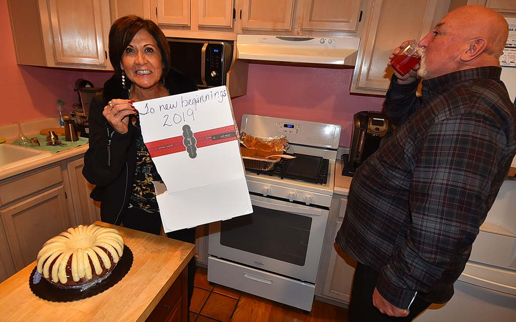 "Isabel Vasquez shows off cake box labeled ""To new beginnings"" at Naranjo-McKercher party as her husband, retired UFCW Vice President Terry Hunt, takes a drink."