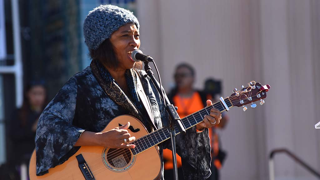 Lisa Sanders performs for the thousands of marchers at the Women's March San Diego.