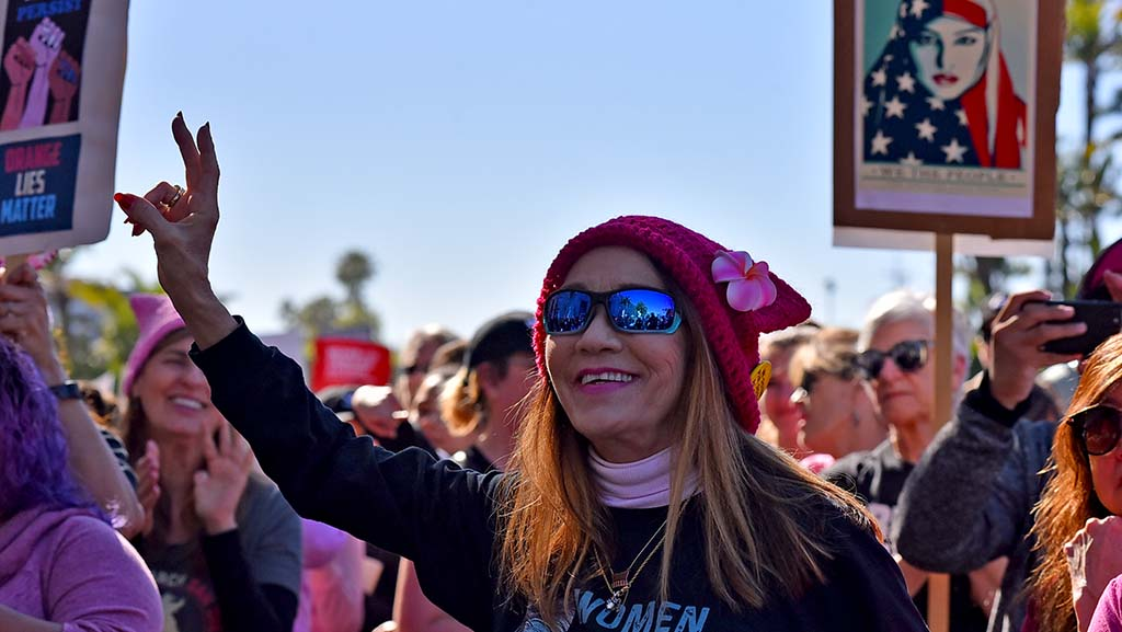 A marcher wearing a pussy hat reacts to a speech at the rally before the Women's March San Diego.