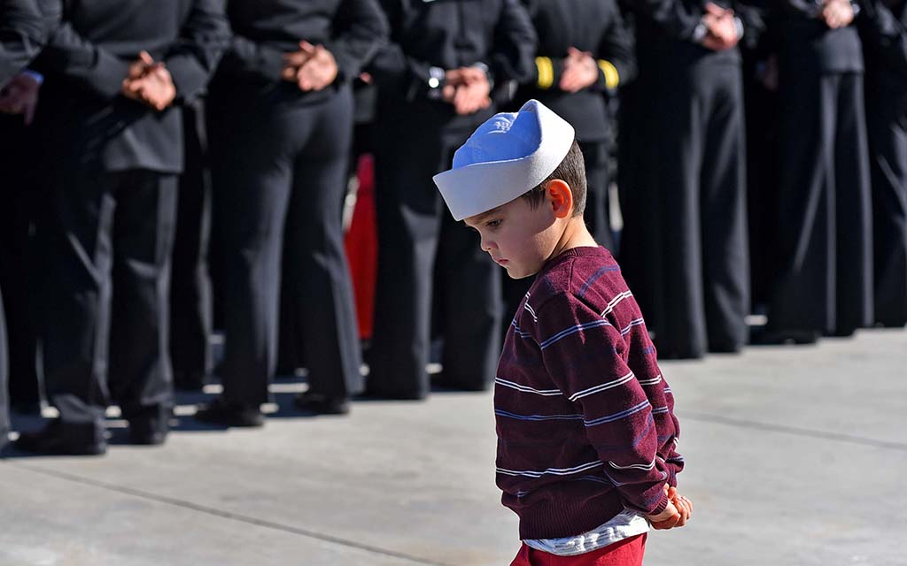 Five-year-old Nicolas Gazca of San Diego, whose mother, Rebecca Church, is a crew member, mimics the sailors of the USS Michael Monsoor before boarding the ship.