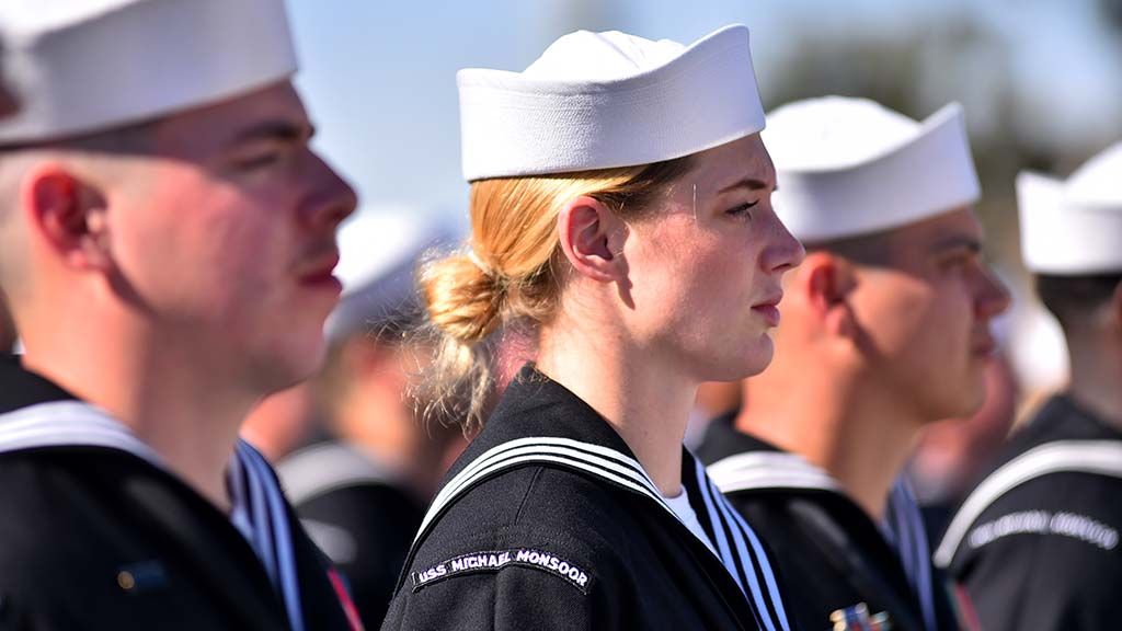 Sailors of the new USS Michael Monsoor observe the commissioning ceremony before boarding the ship.