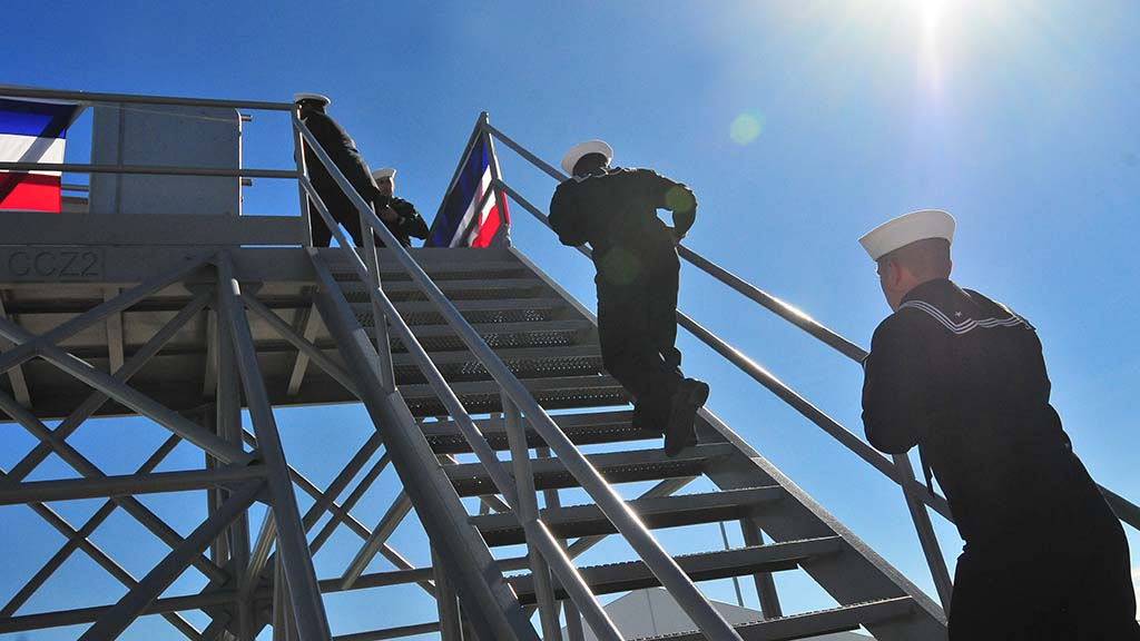 Sailors of the USS Michael Monsoor run up the stairs to board the new ship.