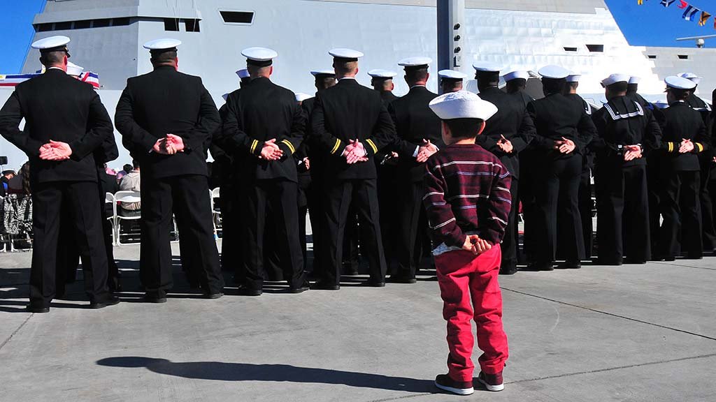 Five-year-old Nicolas Gazca of San Diego, whose mother, Rebecca Church, is a crew member, mimics the sailors of the USS Michael Monsoor before boarding the ship. Photo by Chris Stone