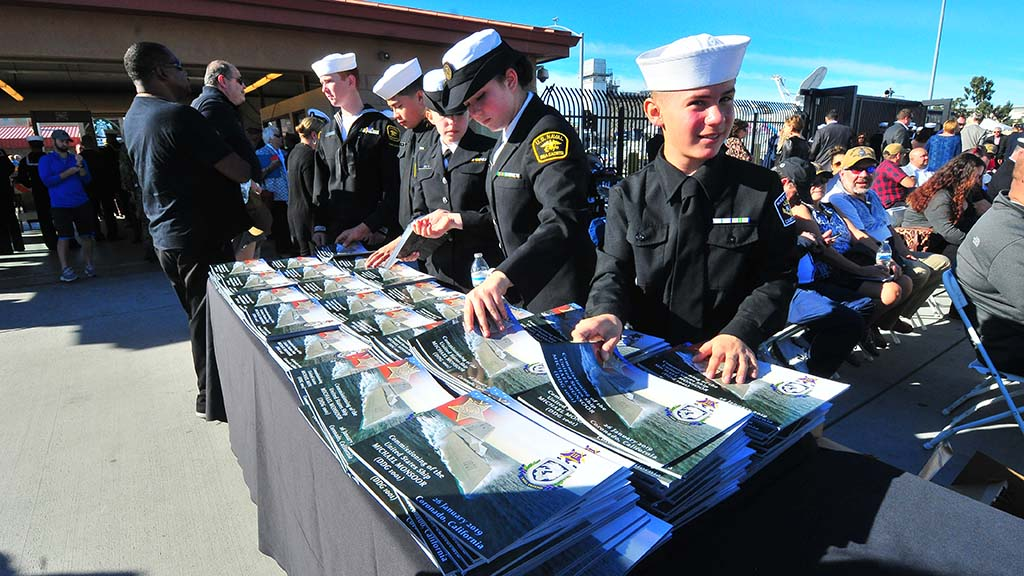 Sea Cadets distribute programs and bottles of water before the ceremony on North Island Naval Air Station.