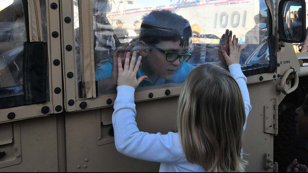 Children get acquainted with the vehicles used by SEALS before the ceremony.