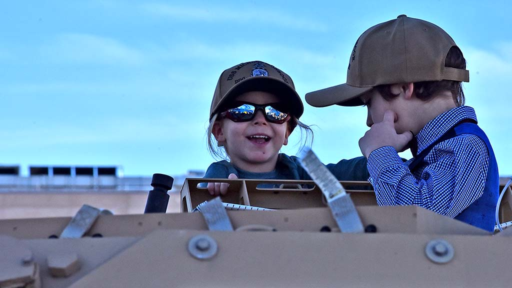Children enjoy checking out the Humvee on display near the ship.