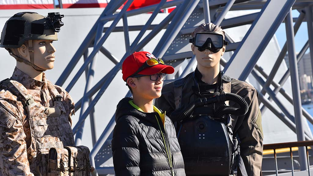 Andrew Zhang, 13, of Canada, poses with uniforms of Navy SEALS that were on display in front of the ship.