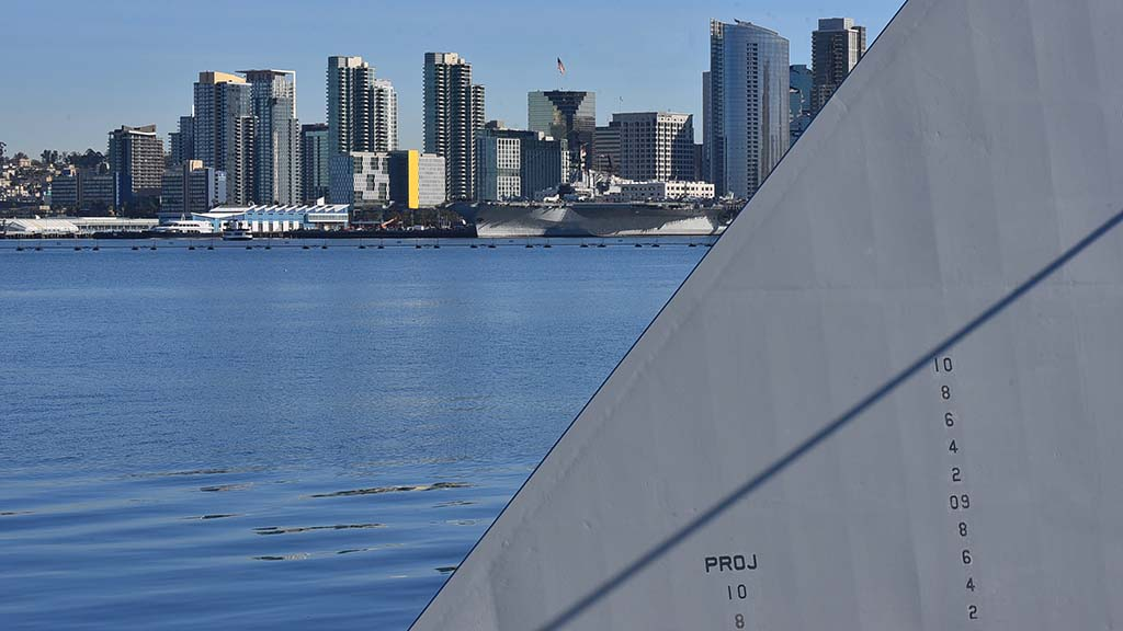 The new destroyer, USS Michael Monsoor, stands ready opposite the San Diego Bay from the San Diego skyline.