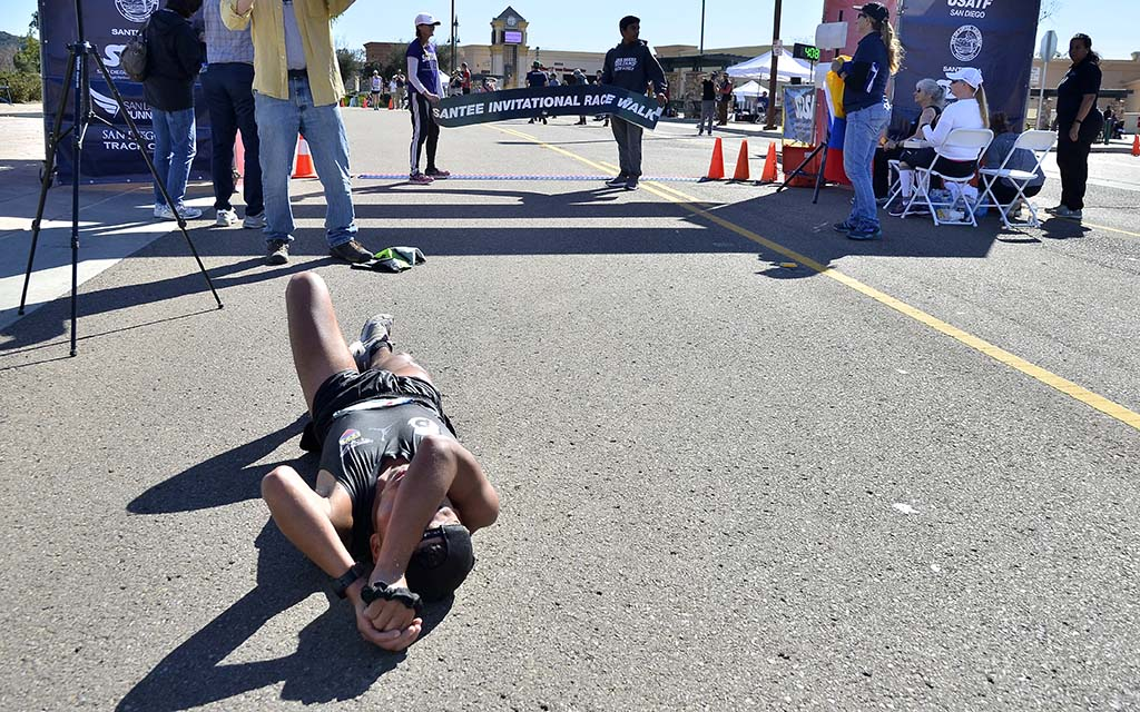 A totally spent David Velasquez rests on ground after finishing 50K in 4:08:32.