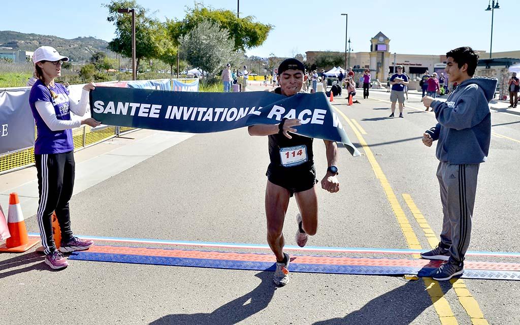David Velasquez breaks through tape to win the Waterbridge Capital International 50km Challenge.