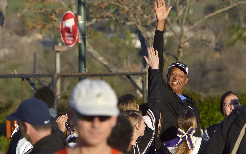 Olympian Willie Banks gives high-fives to Santana High School cheerleaders before start of the concurrent races.