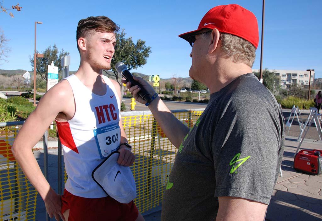 Race director Tracy Sundlun interviews men's 10K walk winner Logan Roberts Jr.