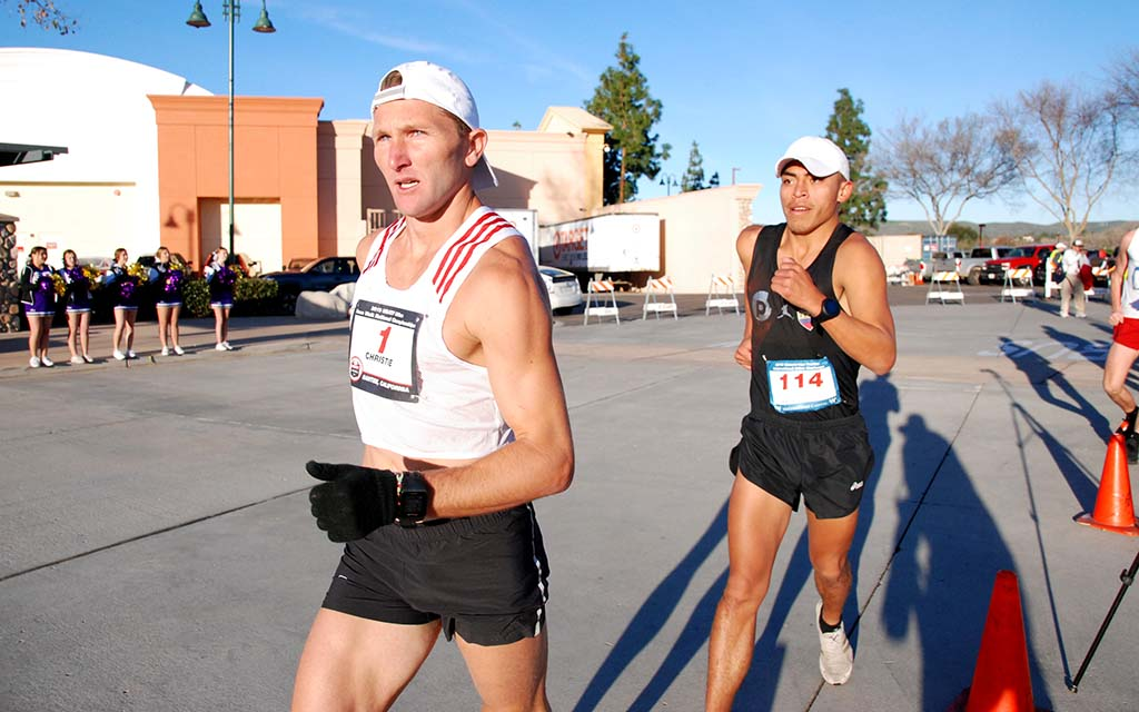 With Santana cheerleaders urging them on, Nick Christie leads David Velasquez early in 50K race.