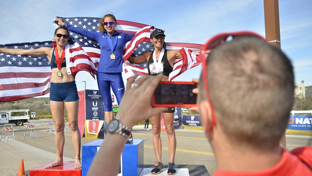 Patrick Casey records medal ceremony for U.S. women's 50K, including his wife, Stephanie, at left.