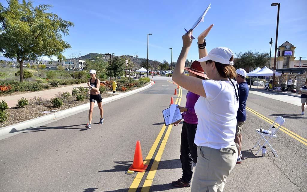 Former 50K race walker Karen Karavanic of Portland, Oregon, officiating at Santee, cheers a 50K finisher.