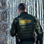 A Border Patrol agent walks along newly installed concertina wire at Border Field State Park.
