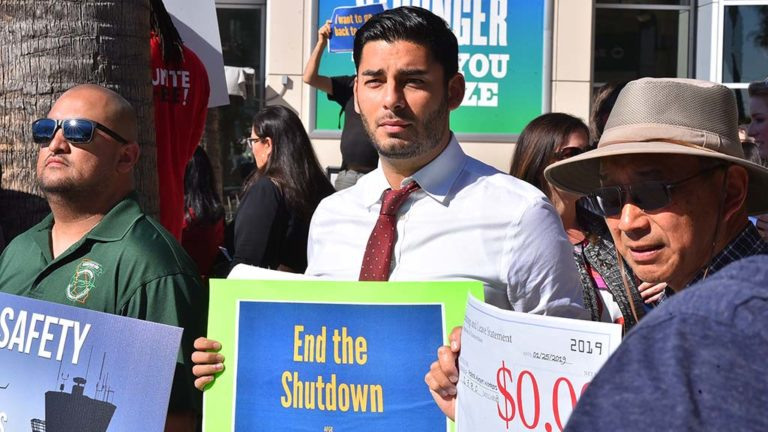Congressional hopeful Ammar Campa-Najjar, wearing tie but not making speech, joins protest at Lindbergh Field.