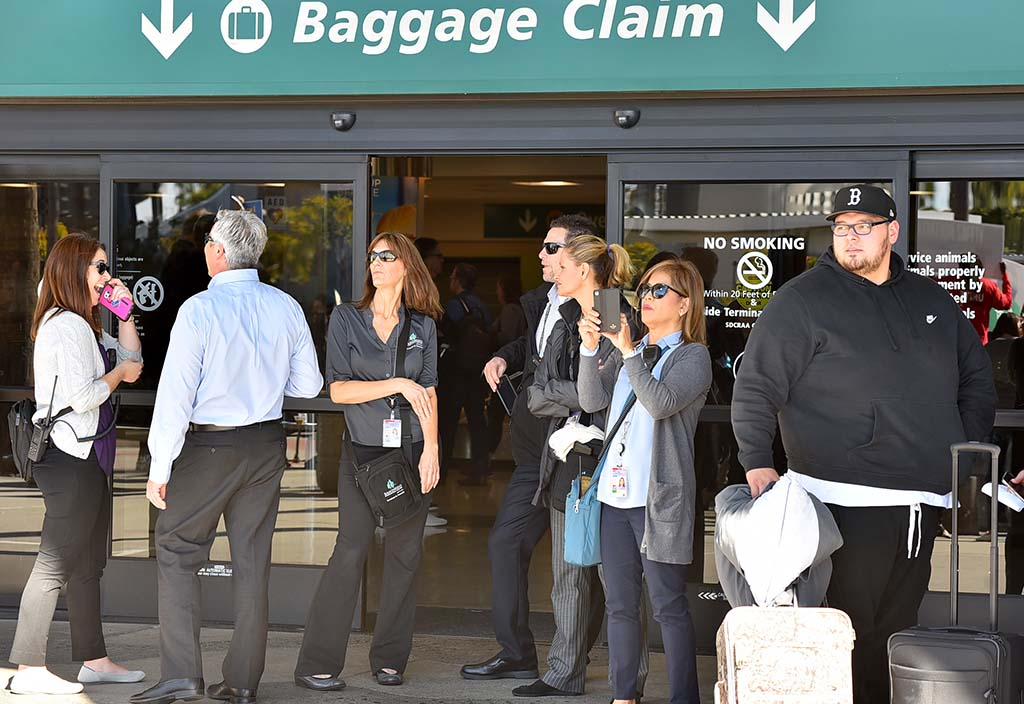 Travelers eye shutdown protest outside Baggage Claim at airport's Terminal 1.