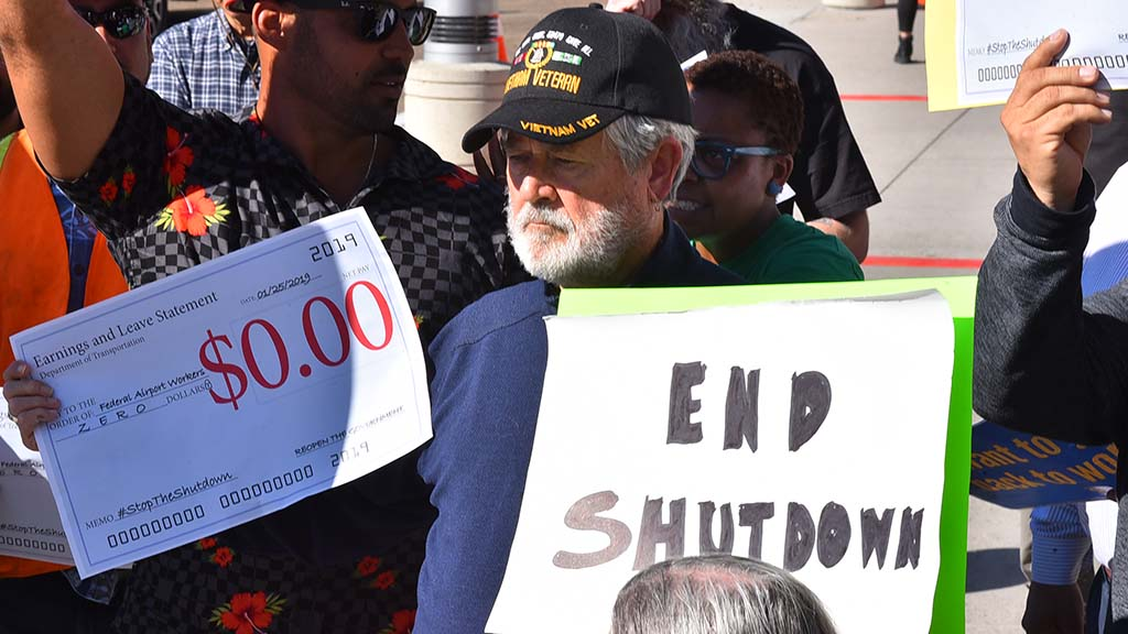 Vietnam veteran holds signs at San Diego airport calling for end to federal shutdown.