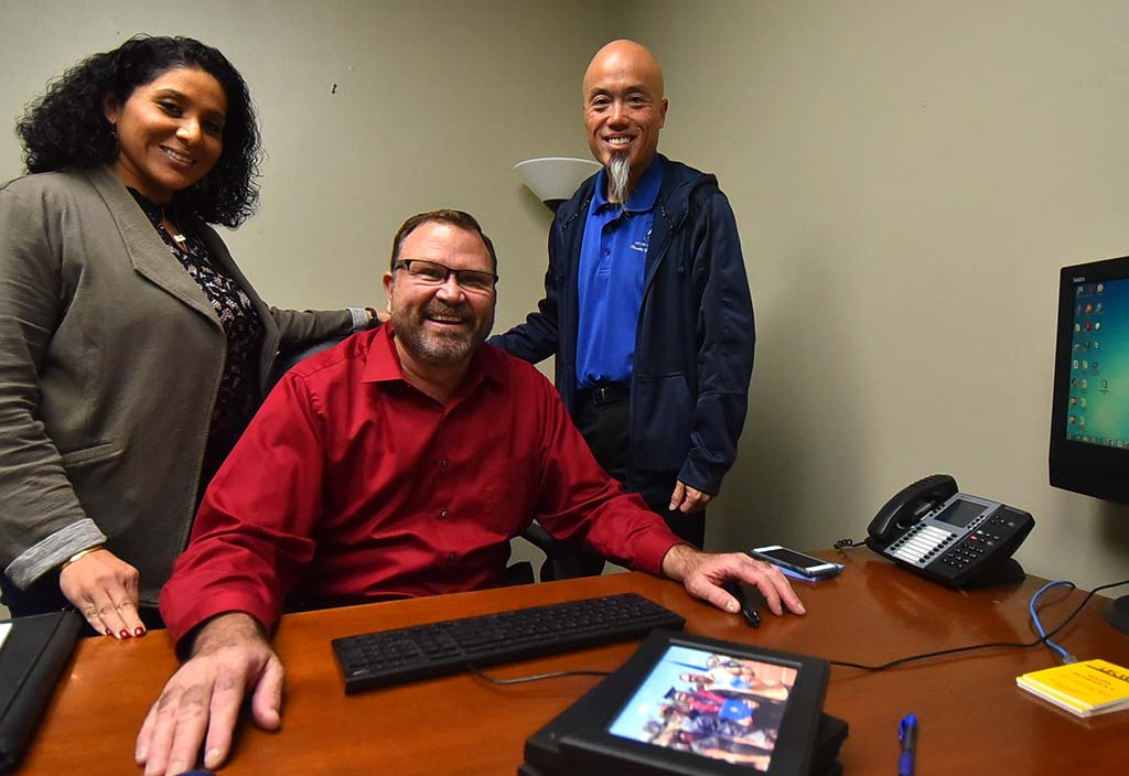 """New Recorder Maribel McKinzie and Secretary-Treasurer Grant Tom stand behind President Bruce """"Todd"""" Walters, who brought photos back to his old office to rehang."""