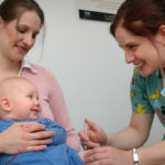 A baby receives a vaccine from a nurse.