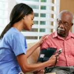 A home health care worker checks a man's blood pressure
