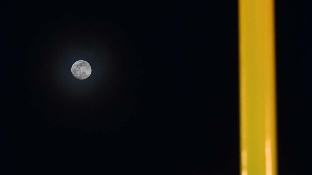 A nearly full moon rises between the goal posts in San Diego at the season opener at SDCCU Stadium.