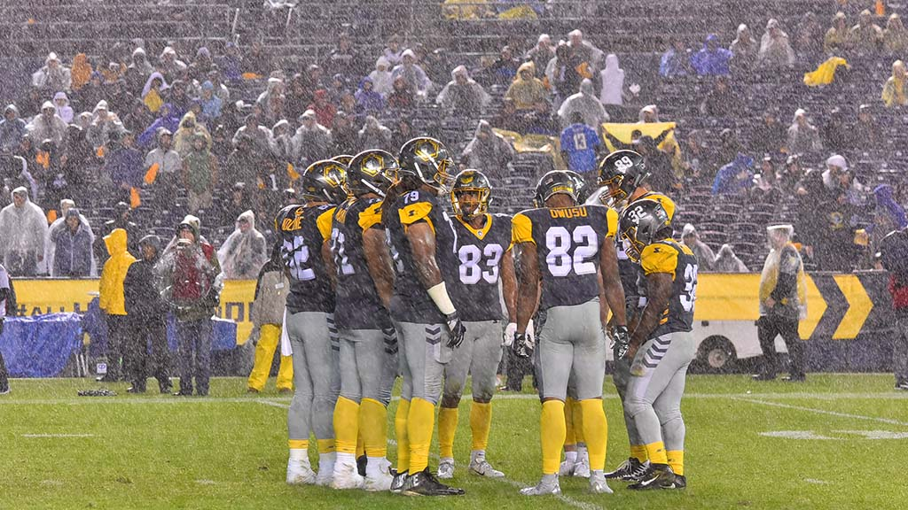 In a steady downpour, San Diego Fleet players await the quarterback for the play call.