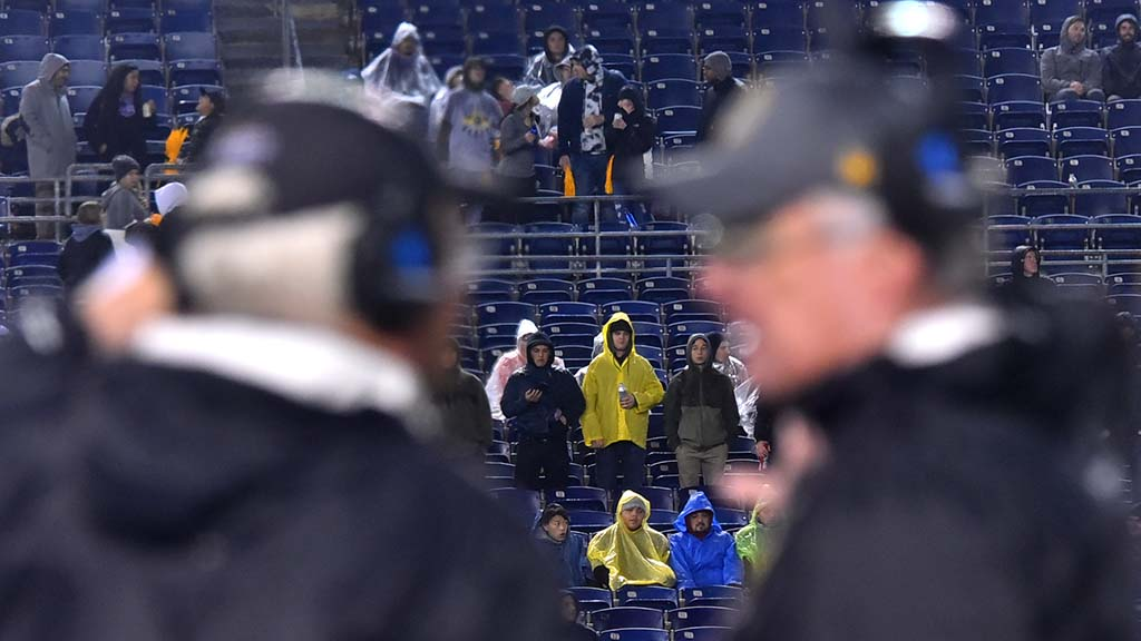 Fans in ponchos watch as Fleet coaches confer.