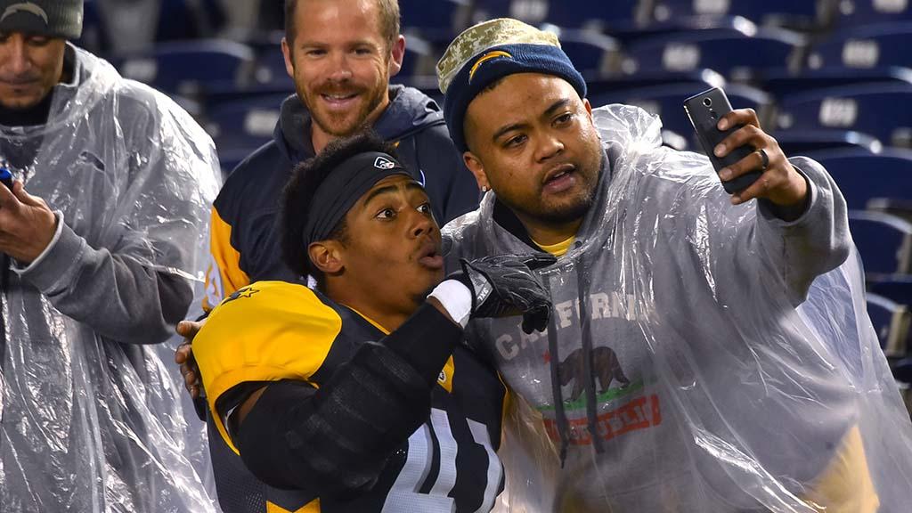 A fan takes a selfie with Fleet outside linebacker Travis Feeney after the game.