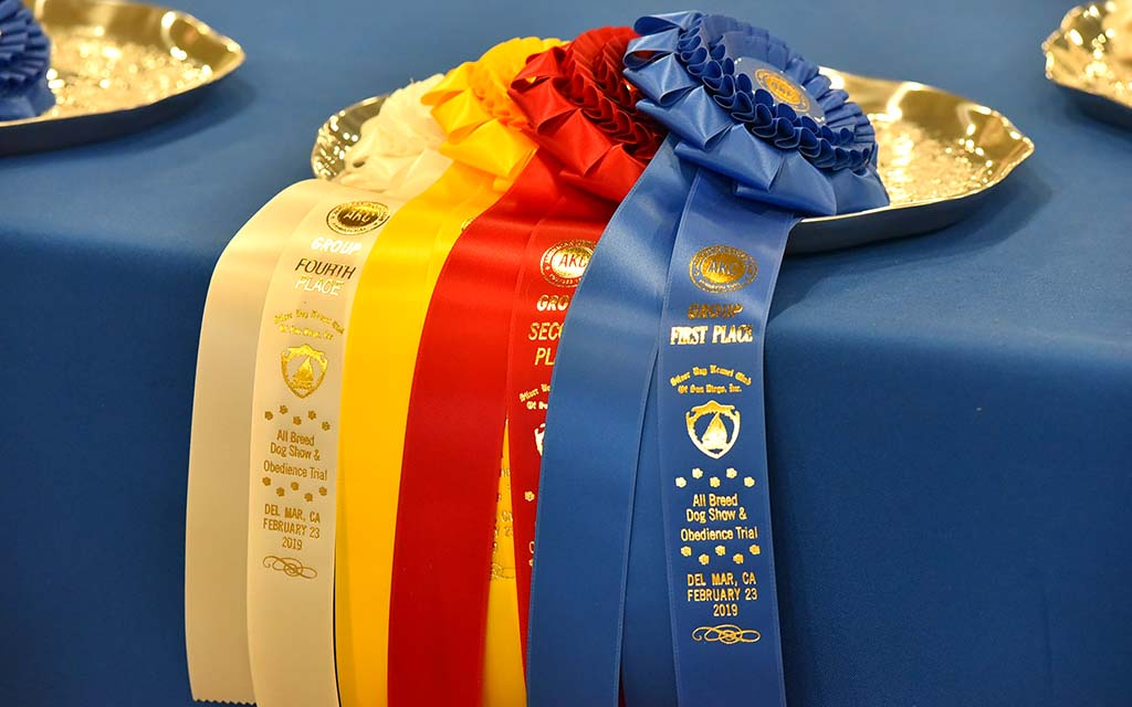 Ribbons are readied for winners in the group competition of the Silver Bay Kennel Club show at the Del Mar Fairgrounds.