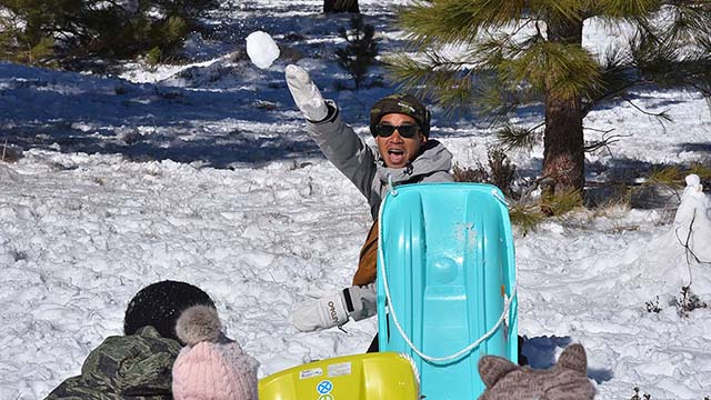 Joseph de la Cruz of Rancho Bernardo and his children enjoy a snowball fight in the Lagunas.