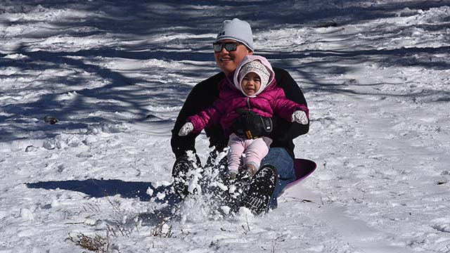 Michael Caaway and his one-year-old daughter Audrey play on the slopes of the Lagunas.