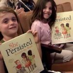 "Seated in the fifth row, Luke and Violet Walsh, 7 and 5, showed off their copies of ""She Persisted Around the World."""